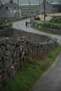 Woman pushing bike uphill on Inishmore